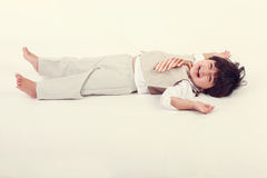 Happy boy. Happy toddler wearin a suit and laying on the floor Royalty Free Stock Photos