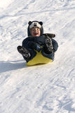 The happy boy. To slide from a hill in the winter Royalty Free Stock Photography