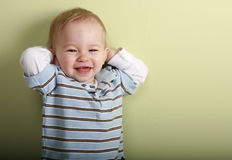 Happy boy. Fourteen month old boy has a playful expression as he stands against a green wall Royalty Free Stock Photo