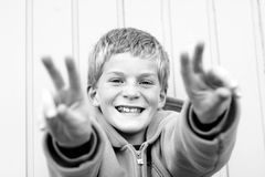Happy boy. Happy young boy, making peace-gesture with his hands Stock Image