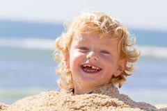 Happy boy. Adorable young happy boy at the beach playing in the sand stock photography