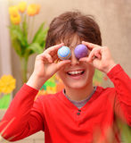 Happy boy anticipate Easter. Portrait of cute boy play with beautiful colorful decorated eggs at home, with pleasure anticipate happy Easter holiday stock photography