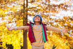 Happy boy with arms outstretched against autumn trees Royalty Free Stock Images