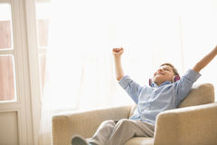 Happy boy with arms raised enjoying music while relaxing on armchair at home Royalty Free Stock Image