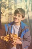 Happy boy with autumn leaves Royalty Free Stock Images
