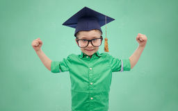 Happy boy in bachelor hat showing power Royalty Free Stock Image