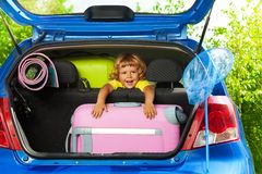 Happy boy with bags in the car. Boy sitting on the back sit with bags and other luggage in the car trunk happy and laughing ready to go on the trip Royalty Free Stock Photo