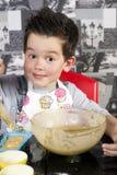 Happy boy baking muffins Stock Photos