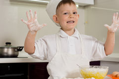 Happy boy baking showing off his floury hands Stock Photo