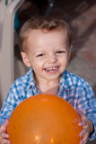 Happy boy with balloon. Happy toddler boy holding an orange balloon Stock Images