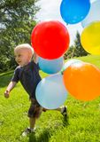 Happy Boy With Balloons Walking In Park Stock Photography