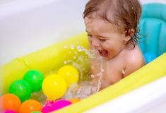 Happy boy bathing. Cute happy little boy bathing in the child`s tub, splashes water and enjoys it, healthy childhood, babies hygiene concept stock photos