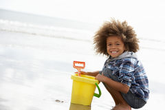 Happy boy at beach with bucket and spade. Smiling at camera stock photo