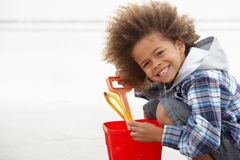 Happy boy at beach with bucket and spade. Smiling at camera royalty free stock images