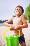 Happy boy on beach. Carrying a bucket of sand Royalty Free Stock Photography