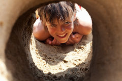 Happy boy on the beach looking through sand castle tunnel Royalty Free Stock Photos