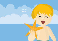 Happy boy on a beach showing a starfish Royalty Free Stock Photo