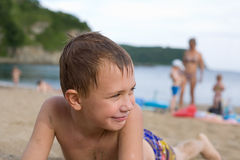 Boy on the beach sunbathing. Stock Photos