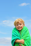 Happy Boy in Beach Towel. A very happy toddler boy wrapped in a beach towel in front of a summer sky Stock Photography