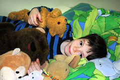 Happy boy with bears. Happy boy  lies in his bed and cuddles with his teddies Stock Images