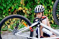 Happy boy in a bicycle helmet repairing his bike Royalty Free Stock Images