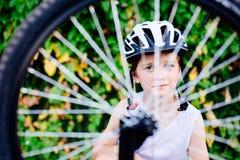 Happy boy in a bicycle helmet repairing his bike Royalty Free Stock Image