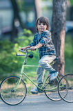 Happy boy with bicycle in the park Royalty Free Stock Photography