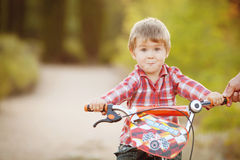 Happy boy on a bicycle in a summer park Royalty Free Stock Photography