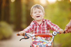 Happy boy on a bicycle in a summer park Stock Images