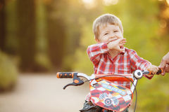 Happy boy on a bicycle in a summer park Royalty Free Stock Photo