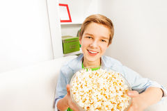 Happy boy with big popcorn bowl on white sofa Royalty Free Stock Photography