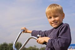 Happy boy on bike. Happy young boy on bike with blue sky and cloudscape background Stock Photos