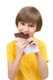 A happy boy is biting a stick of chocolate Stock Photo