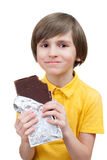A happy boy bits a stick of chocolate Royalty Free Stock Images
