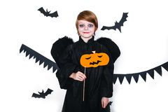 Happy boy in a black angel costume holding a pumpkin Stock Photos