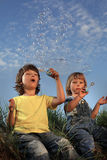 Happy boy blowing bubbles on nature. Two happy boy blowing bubbles on nature Royalty Free Stock Image