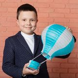 Happy boy in blue jacket holding a balloon in his hands and smiling, concept of travel. And education royalty free stock photo