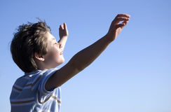 Happy boy and blue sky. Happy young boy celebrating with arms in air and blue sky background Stock Photos