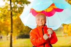 Happy boy with blue umbrella standing under rain Stock Photography
