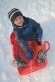 Happy boy on bob sleigh. Little boy smiling while sitting on winter bob sleigh Royalty Free Stock Photo