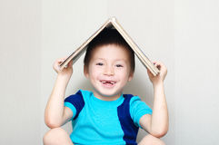 Happy boy with book on head making roof Royalty Free Stock Photos