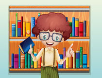 A happy boy with a book standing in front of the bookshelves Stock Photo