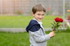 Happy boy with a bouquet of roses Stock Image
