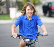 Smiling Boy Riding Bike. A happy boy with brown hair and eyes, wearing a blue shirt, smiles as he rides his bike on a suburban neighborhood street Stock Images