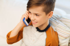 Happy boy calling on smartphone at home Stock Photos