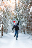 Happy boy in a cap of Santa Claus in the winter forest. Royalty Free Stock Image