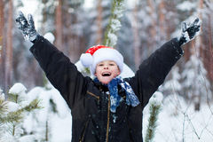 Happy boy in a cap of Santa Claus in the winter forest. Stock Photo