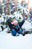 Happy boy in a cap of Santa Claus in the winter forest. Stock Image