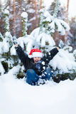 Happy boy in a cap of Santa Claus in the winter forest. Stock Photos