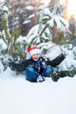 Happy boy in a cap of Santa Claus in the winter forest. Royalty Free Stock Images